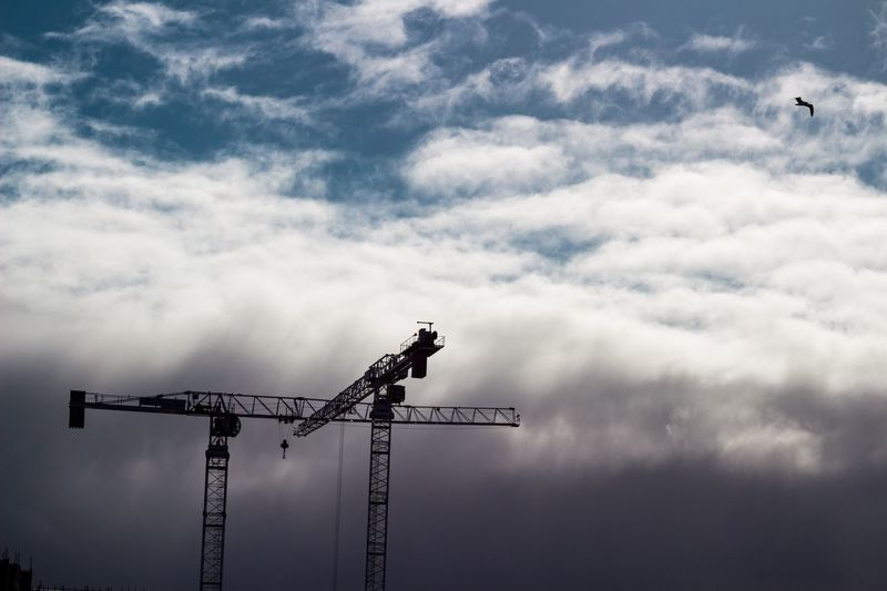 Silhouette cranes at construction site against cloudy sky