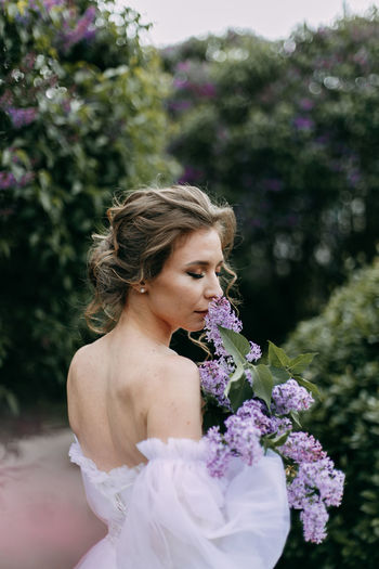A delicate elegant young woman bride in a wedding dress walks in a blooming spring outdoor park