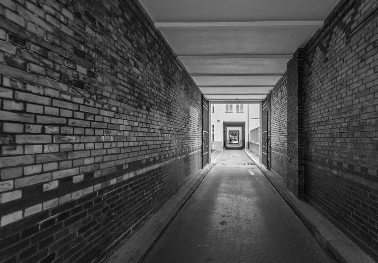 Empty narrow corridor along buildings