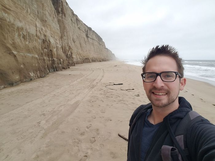 Portrait Of Smiling Mid Adult Man Standing At Beach Against Cloudy Sky