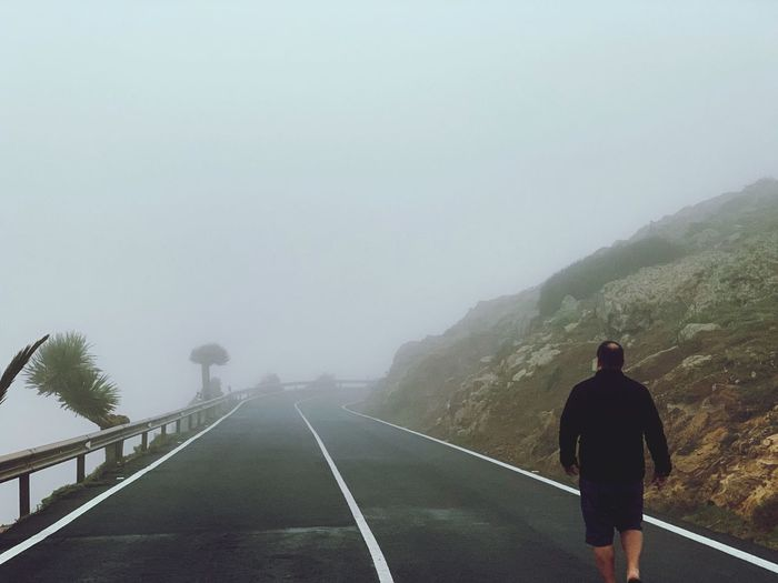 Rear view of man walking on road during foggy weather against sky