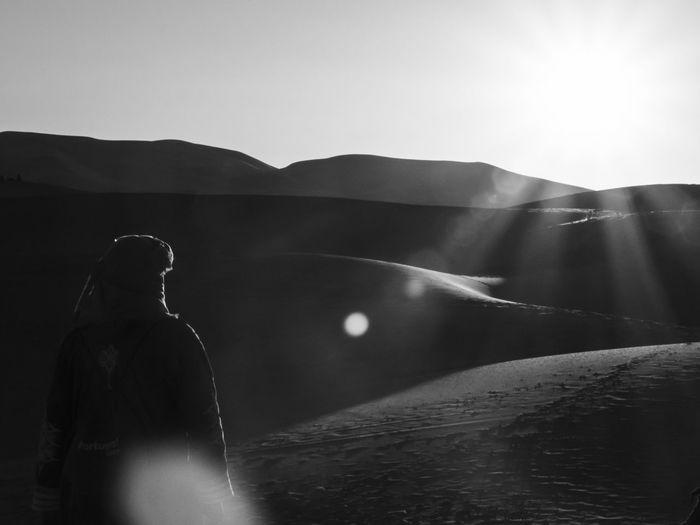 Rear view of man on a desert dune against sky