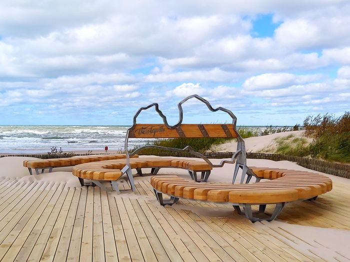 Lounge chairs by swimming pool at beach against sky