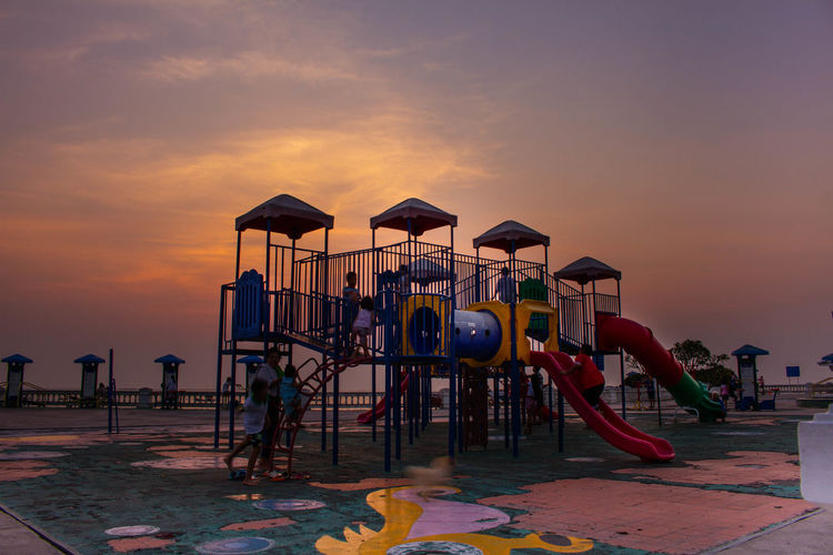 Children Playing On Slide Against Cloudy Sky