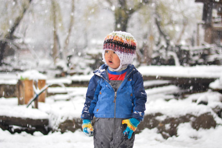 Cute Boy Standing On Snow Covered Field Looking Away