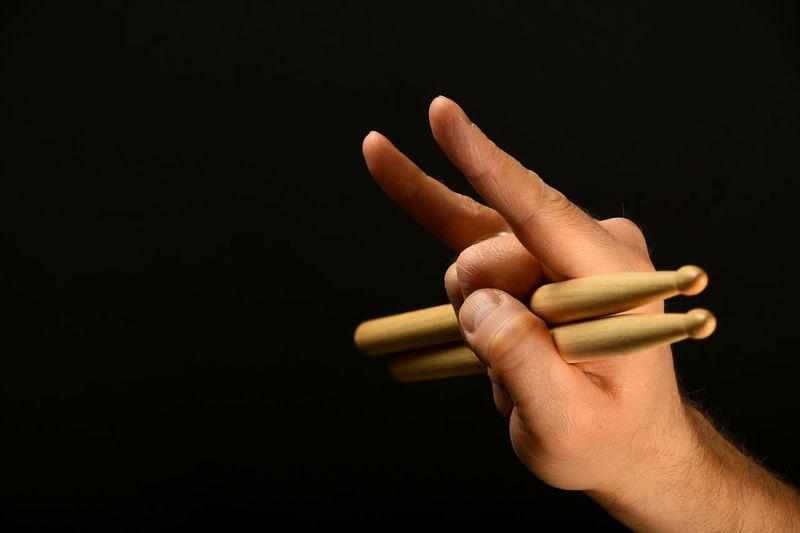 Cropped Hand Gesturing Drumsticks Against Black Background