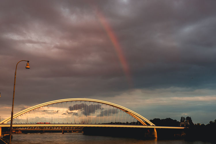 Low angle view of rainbow over bridge against sky