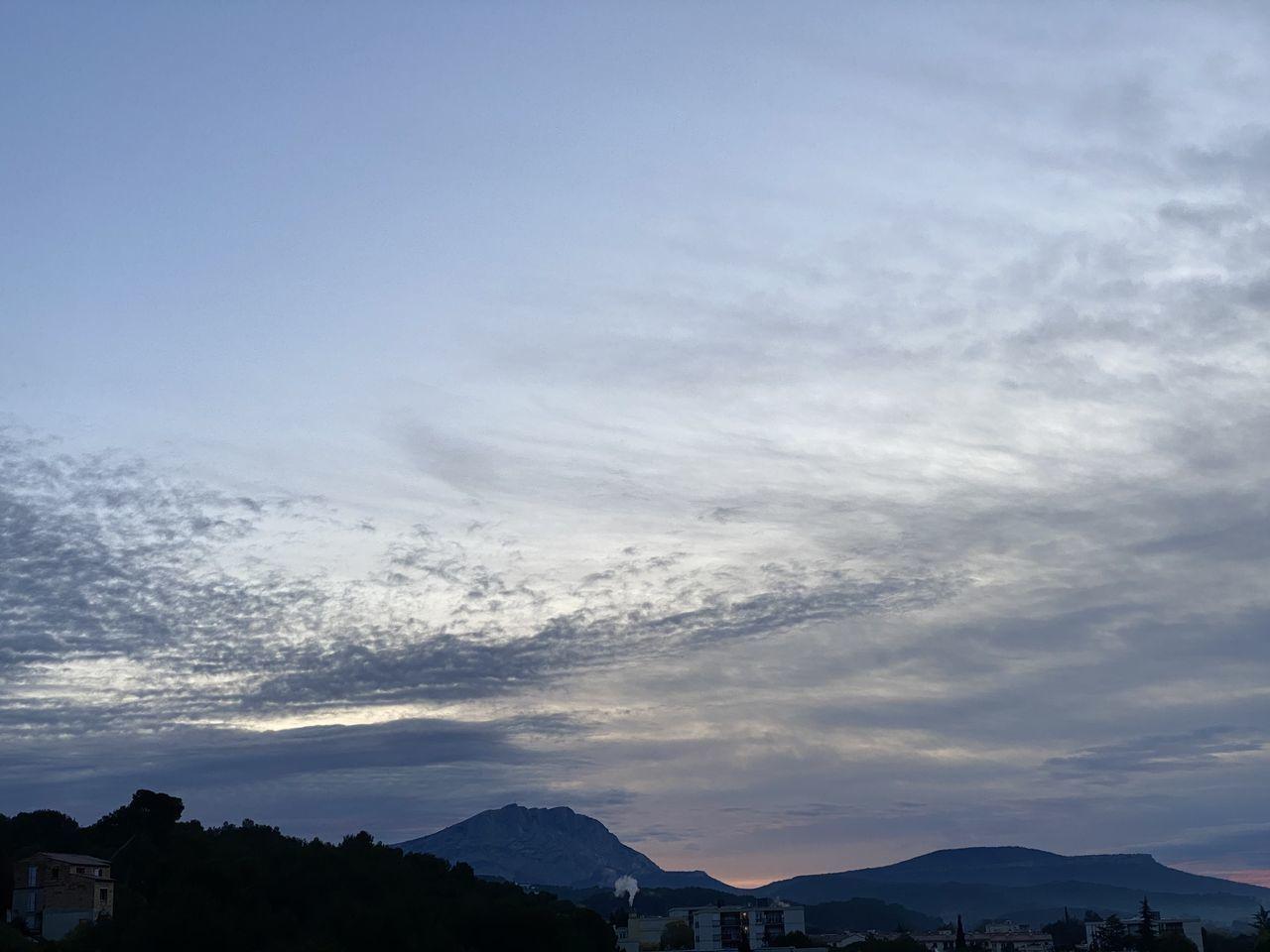 cloud - sky, sky, mountain, scenics - nature, beauty in nature, tranquility, tranquil scene, mountain range, nature, sunset, silhouette, no people, non-urban scene, idyllic, outdoors, environment, landscape, day, building exterior, mountain peak