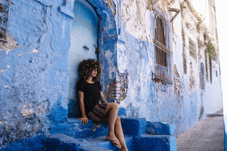 Beautiful woman sitting outside building