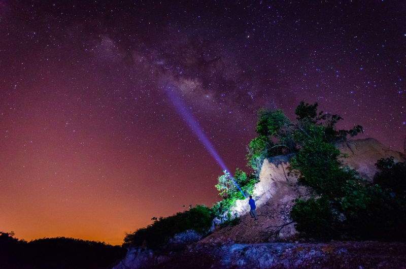 Low angle view of man climbing on rock formation against star field