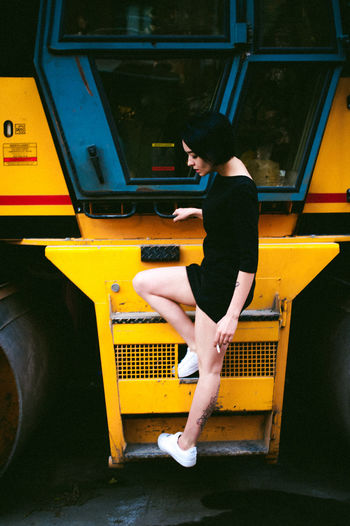 Day Full Length Land Vehicle Leisure Activity Lifestyles Mode Of Transport One Person Outdoors Public Transportation Real People Side View Transportation Yellow Young Adult Young Women