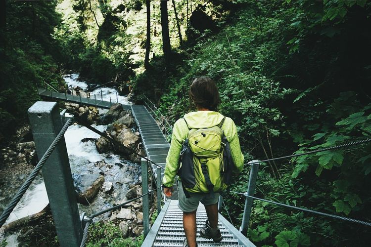 Rear view of woman walking on footbridge over waterfall in forest