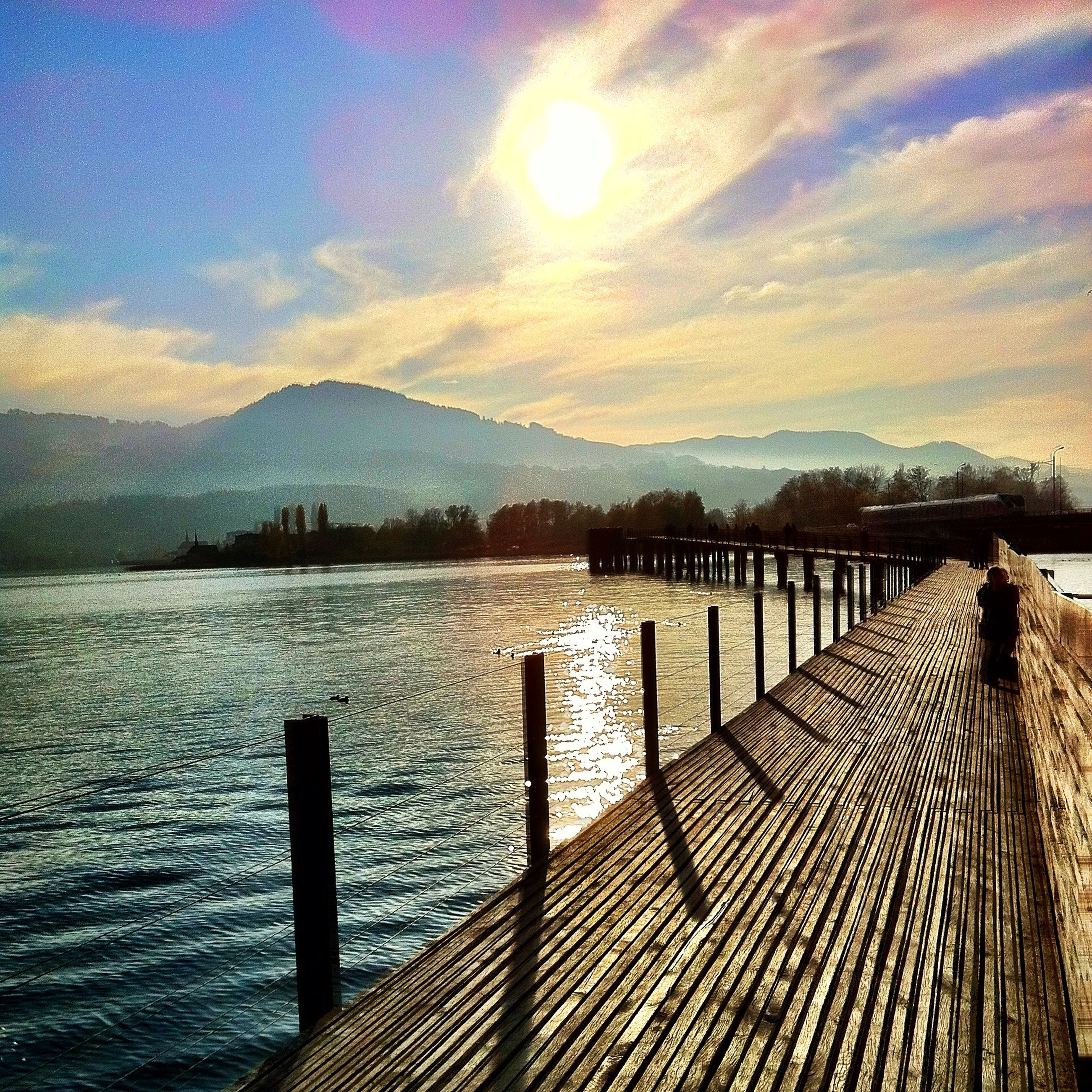 water, pier, railing, sky, tranquil scene, mountain, tranquility, scenics, sea, jetty, the way forward, built structure, beauty in nature, sunset, nature, mountain range, lake, boardwalk, cloud - sky, wood - material