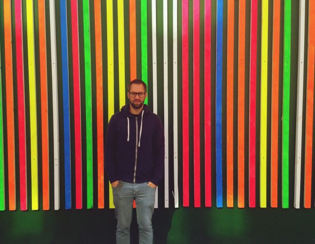 Portrait of young man standing against colorful patterned wall