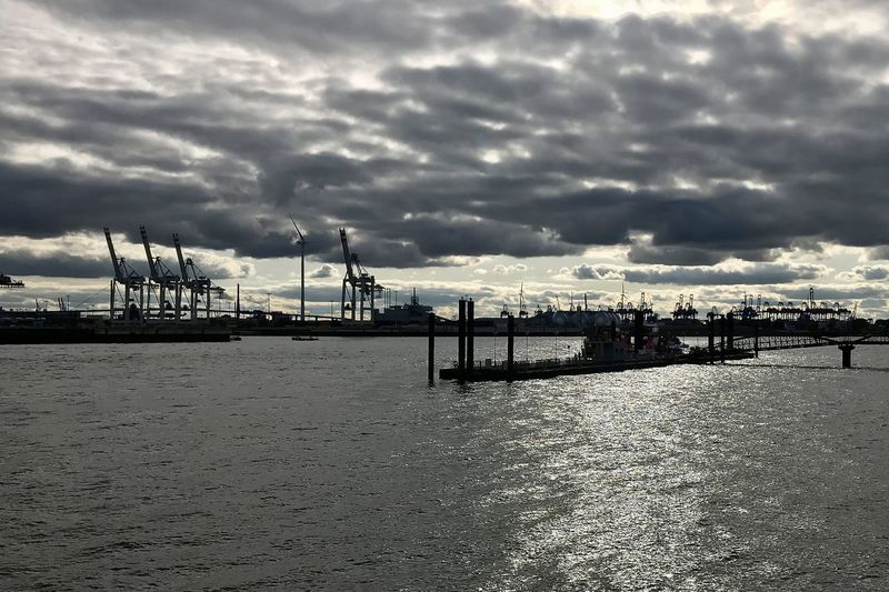Pier at harbor against cloudy sky