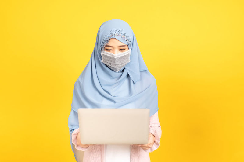 Portrait of a teenage girl against yellow background