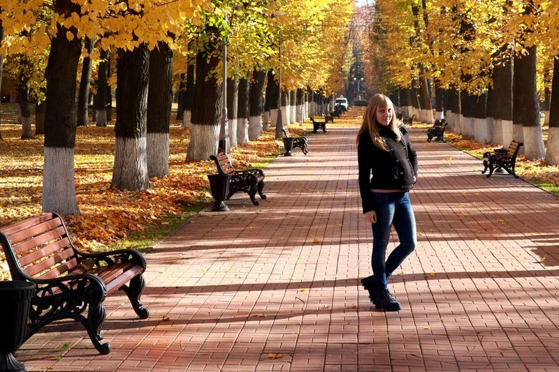 Full Length Portrait Of Woman Standing On Footpath In Park During Autumn