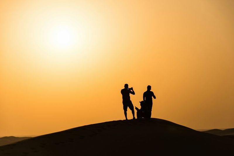 Silhouette men standing on desert during sunset