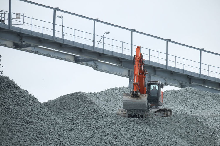 Doel, Antwerp, Belgium – February 2019: Red crane on a huge pile of gravel working to put the gravel on a transporting conveyor Industry Transportation Construction Industry Machinery Construction Site Sky Nature Day Construction Machinery Development No People Outdoors Architecture Connection Earth Mover Built Structure Clear Sky Equipment Land Vehicle Bridge Quarry Construction Equipment