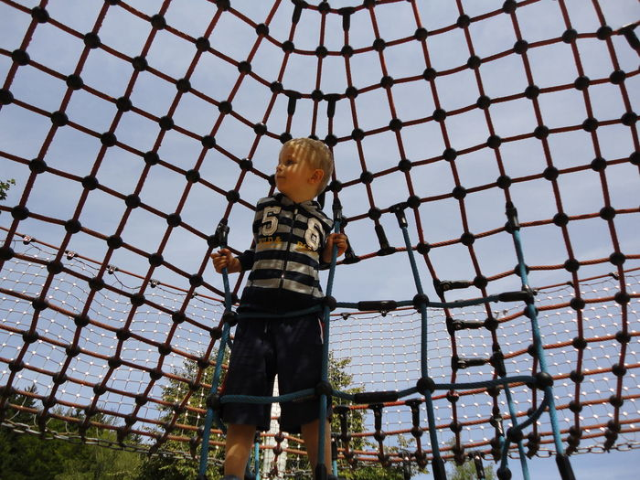 Boy Climbing Rope Against Sky At Park