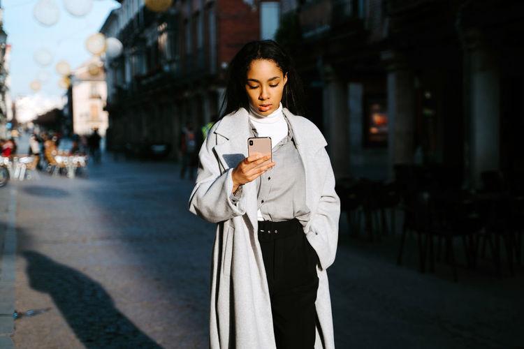 Full length of man holding mobile phone standing on street