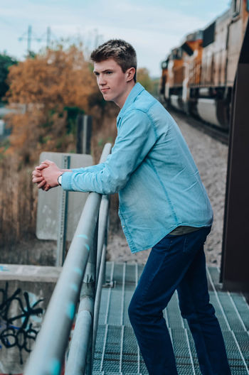 Side view of young man standing by railing against railroad track