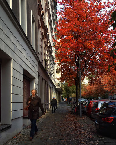 People walking on street amidst buildings during autumn