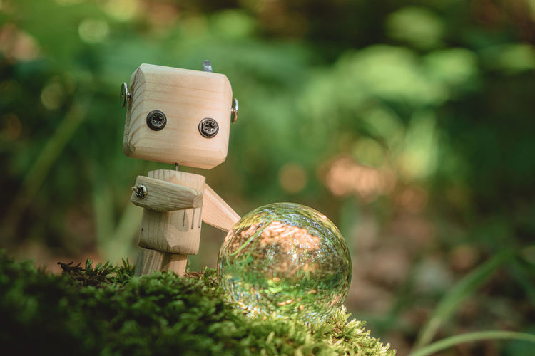 Environment concept, a wooden robot, crystal ball, on moss in the forest, environmental protection.