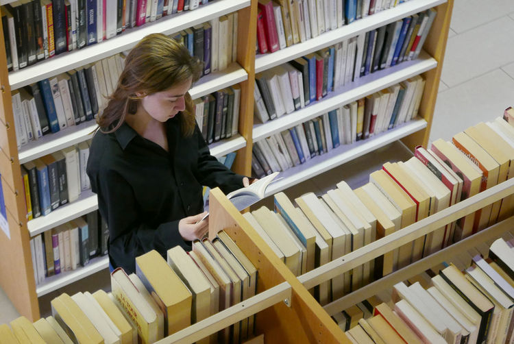 Close-up of young woman reading book in library
