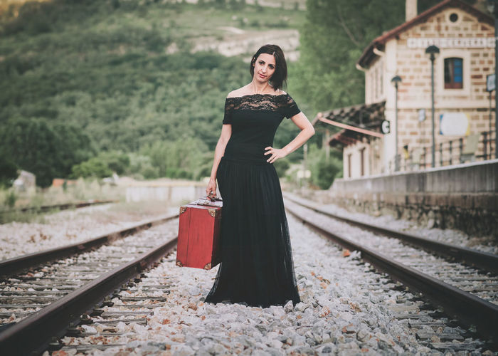 Portrait of woman with luggage standing on railroad track