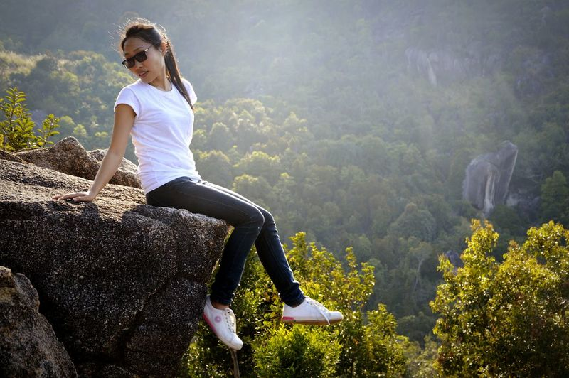Full length of woman wearing sunglasses sitting on rock formation