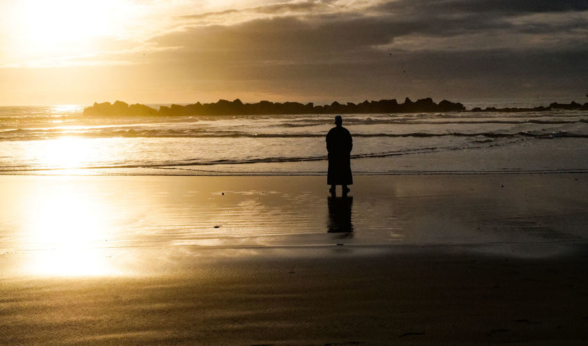 sunset Beach Sky Water Land Real People Silhouette Sea Sunset One Person Reflection Nature Beauty In Nature Standing Full Length Tranquility Rear View Cloud - Sky Tranquil Scene Outdoors Agadir