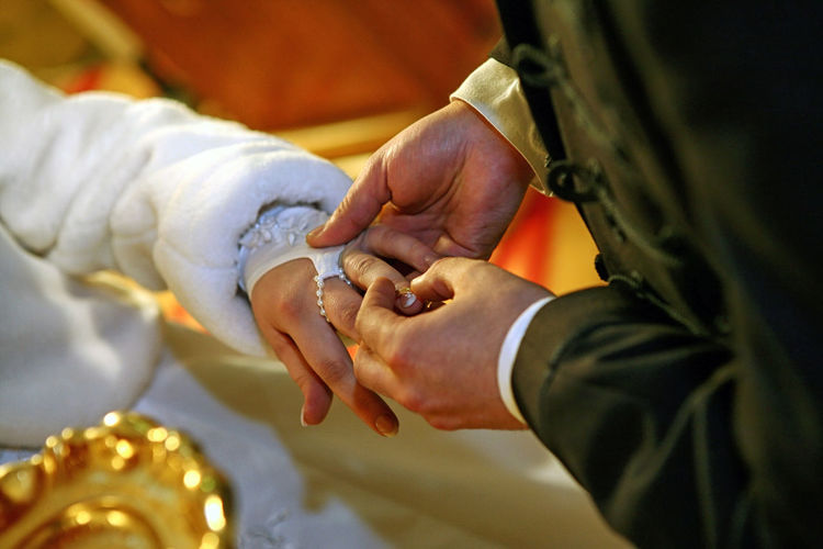 Groom putting a ring on bride's finger during wedding ceremony. Couple Engagement Forever Gold Jewelry Happy Love Marriage  Pearl Spouse Two Wedding White Woman Male Female Communion Romantic Symbol Human Hand Bridegroom Bride Ceremony Togetherness Men Wedding Ceremony Wedding Religion Life Events Traditional Ceremony