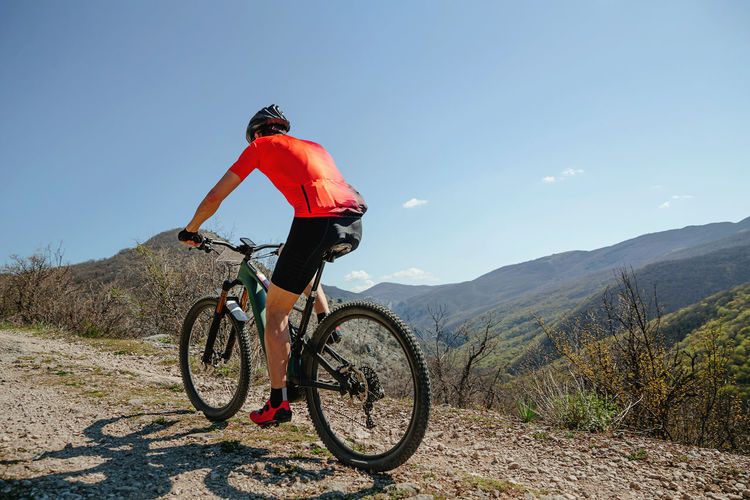 Man on bicycle riding mountain trail in background blue sky and mountains