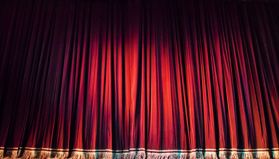Red Closed Curtain With Spotlight In Theater