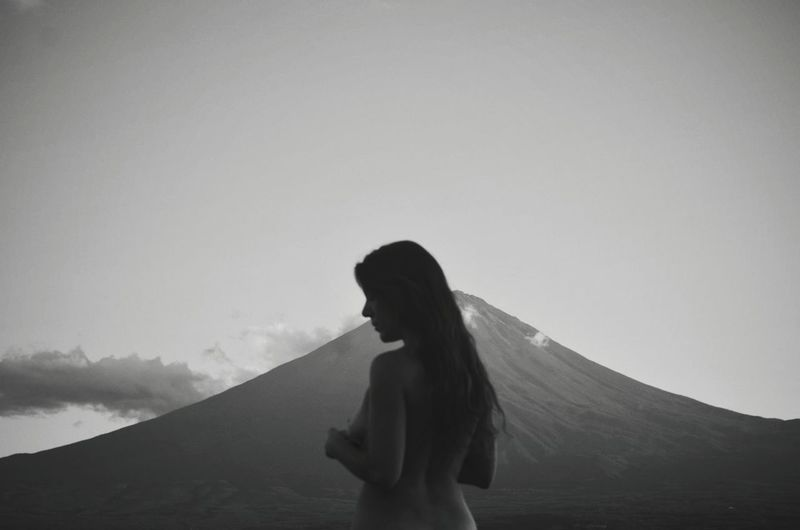 Rear View Of Shirtless Woman Standing Against Mountain And Sky During Dusk