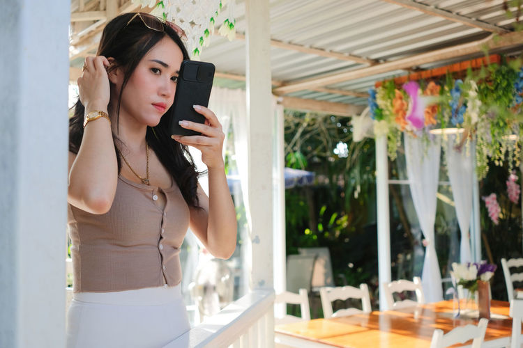 Young woman using mobile phone while standing outdoors