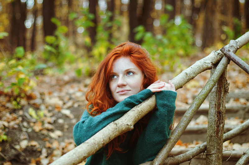 Portrait of happy redhead woman with arms raised in forest