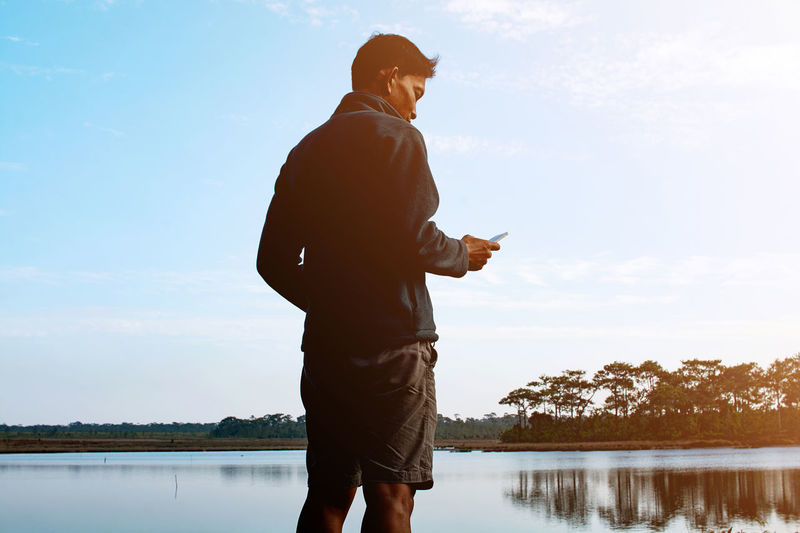 Man using mobile phone while standing in lake against sky