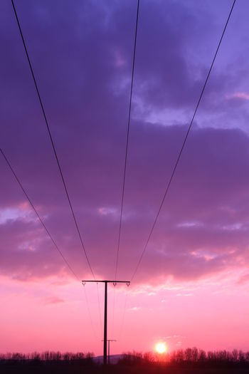 Silhouette telephone pole on field against sky during sunset