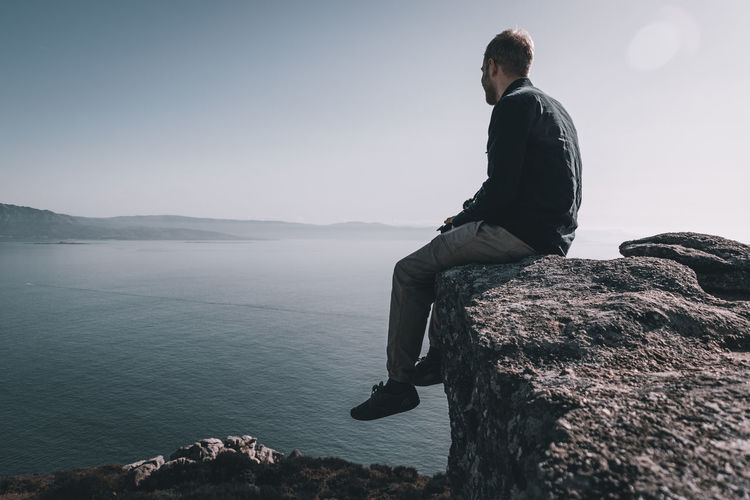 Man sitting on rock looking at sea and mountain against sky