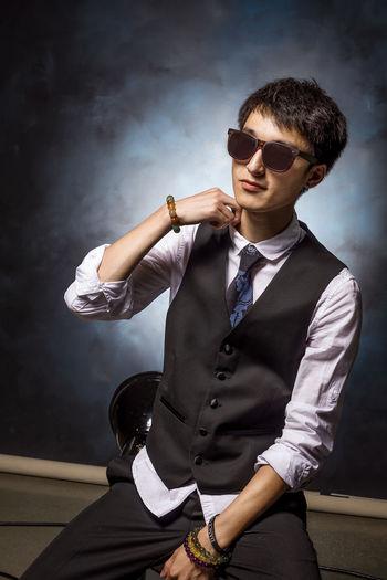 Stylish man sitting against wall