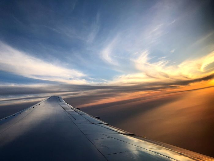 Airplane flying over clouds during sunset