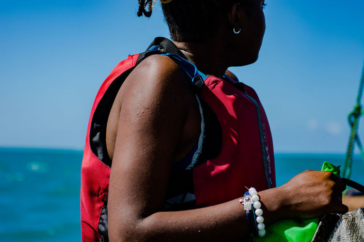 Midsection of woman by sea with a life jacket against blue sky