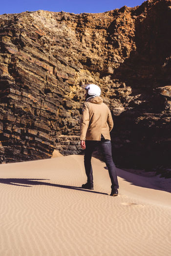 Man Adult Sunlight Desert Arid Climate Rock Formation Walking Helmet Exploring Adventure Searching Sand Sand Dune Men One Person Stylish Model Travel Looking Away Going Away Shadow Moon Another World Rock South