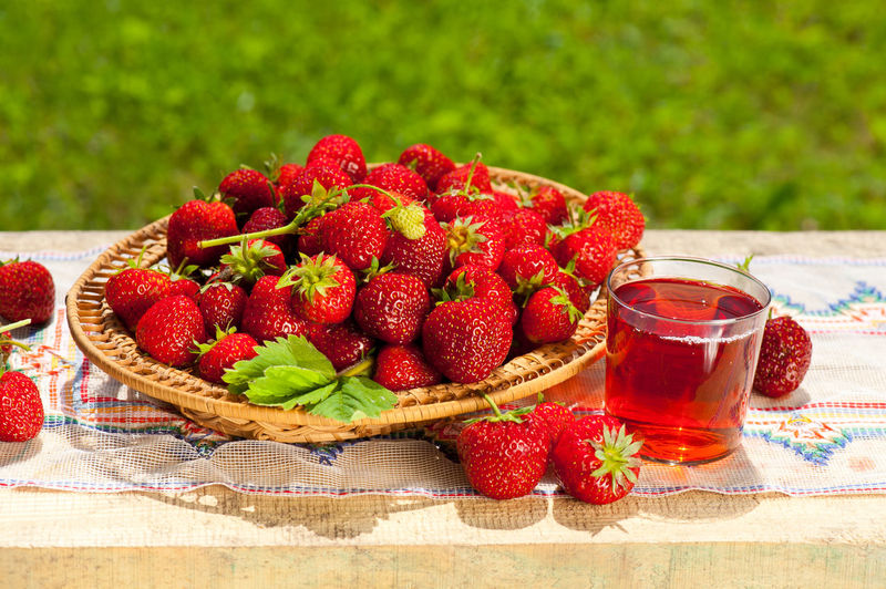 Fresh ripe strawberries in basket and juice in glass on wooden board, horizontal orientation, nobody in frame, photo taken in garden in open air, sunny day. Basket Beverage Compote Cup Drink Food Fruit Fruits Glass Healthy Eating Heap Juice Leaf Mug No People Pile Ready-to-eat Red Strawberries Strawberry