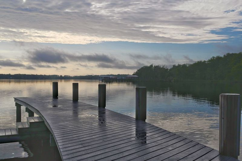 Wooden pier on lake against sky