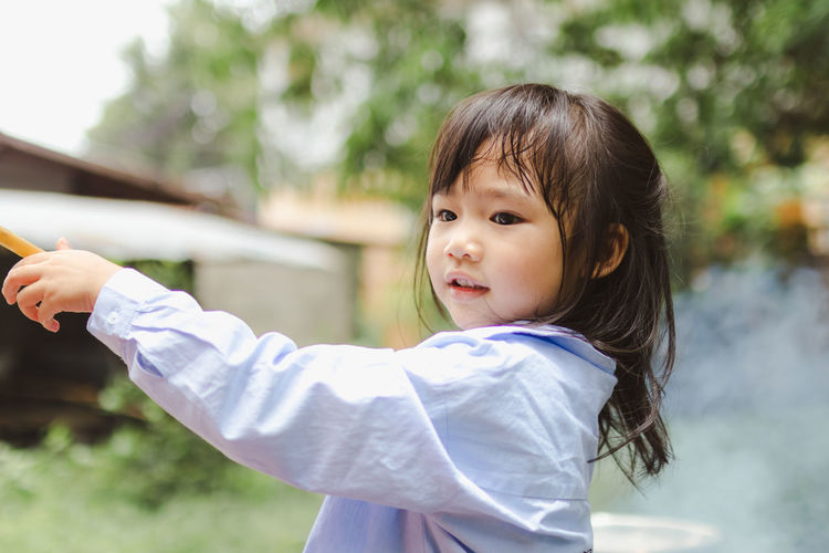 Bangs Casual Clothing Child Childhood Cute Day Females Focus On Foreground Girls Hairstyle Innocence Leisure Activity Lifestyles One Person Outdoors Portrait Real People Standing Waist Up Women