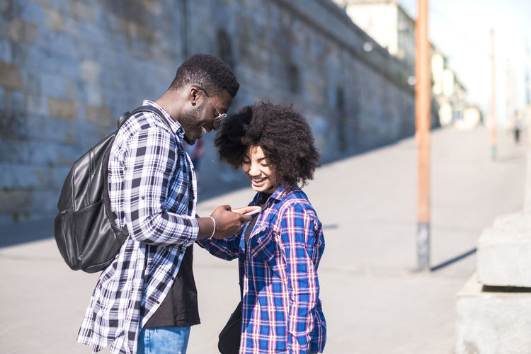 Couple of people man and woman young laughing looking a phone together - happy couple in the city enjoyig the leisure outdoor activity - first date love concept for millennials Togetherness Two People Men Bonding Emotion Real People Adult Love Lifestyles People Smiling Women Focus On Foreground Casual Clothing City Leisure Activity Architecture Standing Males  Day Positive Emotion Outdoors Couple - Relationship CheckedShirt Enjoying Life Millennial Beautiful People Music Listening To Music Eyeglasses  20-24 Years Technology Mobile Phone Boyfriend Girl Afrohair