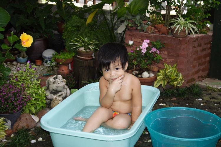 Portrait of shirtless boy sitting in bathtub at yard